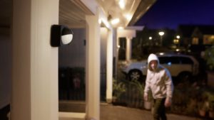 Philips Hue Outdoor Motion Sensor installed outdoors overlooking a home